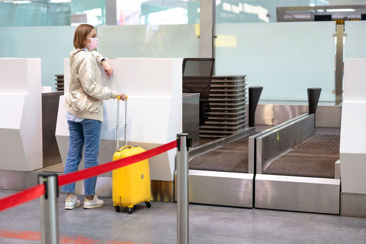 Full length of woman with luggage standing at airport