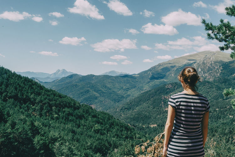 Girl walking along a small path in the mountain of spain. on a sunny summer day