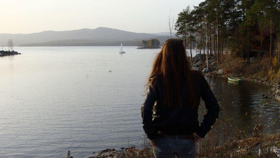 Rear view of woman standing at shore of lake turgoyak