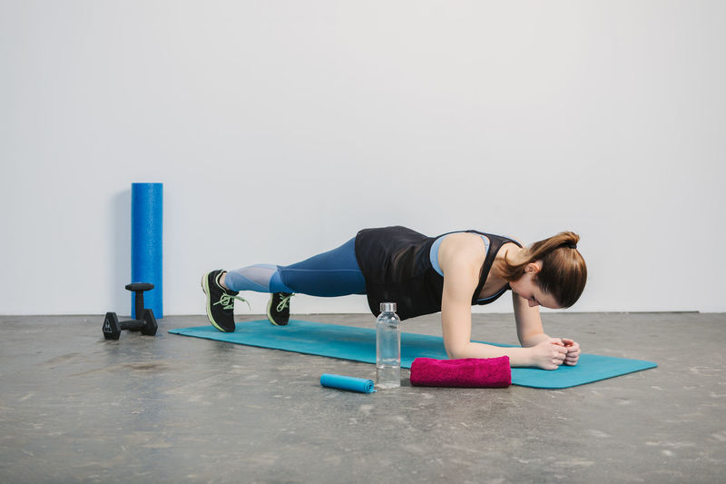 Young woman practicing plank pose Exercising Healthy Lifestyle Wellbeing Sports Clothing Lifestyles Sport Full Length Indoors  Strength One Person Gym Young Adult Young Women Body Care Women Exercise Mat Vitality Sports Training Exercise Equipment Effort Physical Activity Body Conscious Fitness Workout Working Working Out Inside Photography Horizontal Sport Clothes Sport Clothing Athlete