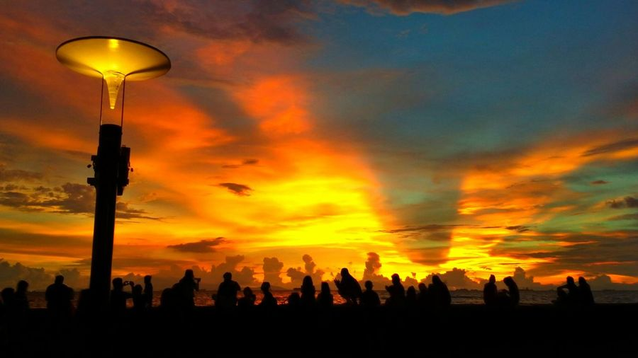 Silhouette people against dramatic sky during sunset