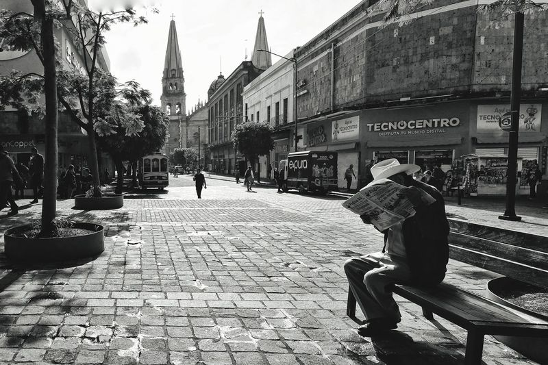 People sitting on footpath by buildings in city