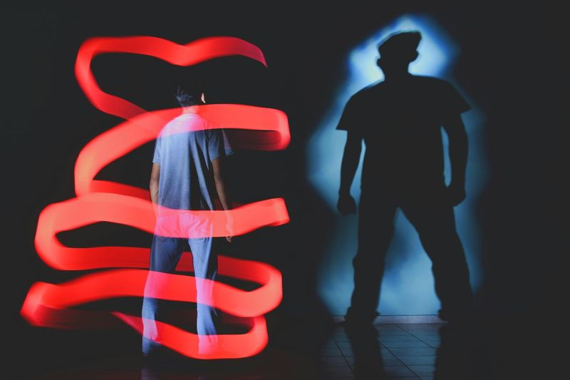 Rear view of silhouette man standing against illuminated background