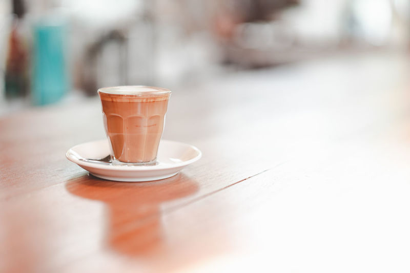 small cup of piccolo latte served on wooden table with copy space on right, monotone Bar Barista Beverage Brown Cafe Caffeine Coffee Copy Cup Drink Fresh Glass Hot Latte Milk Piccolo Relax Retro Serve Small Space Table Tone