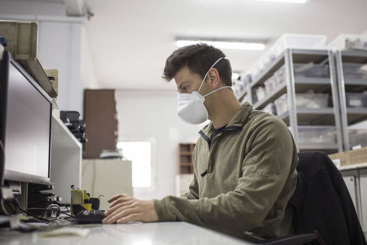 Man working on table with mask