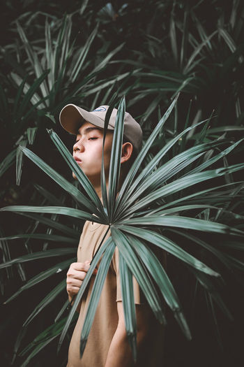 Shirtless man standing by plants