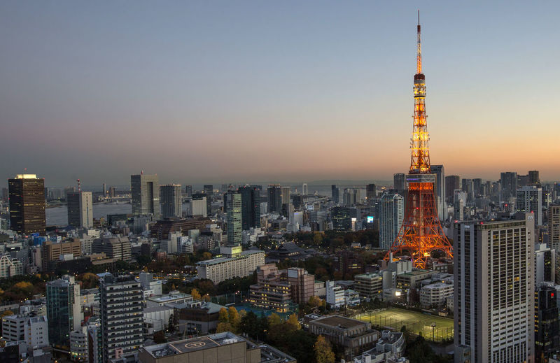 Illuminated tokyo tower in city against clear sky during sunset
