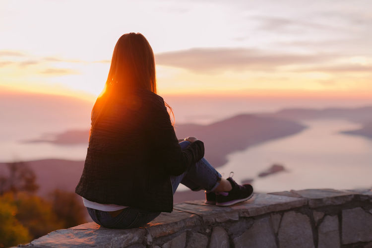 woman relax in mountains at sunset view. Vacations and travelling Hiking Relaxing Top Travelling Vacations Woman Brunette Casual Clothing Day Enjoying Life Leisure Leisure Activity Lifestyles Montenegro Mountain Mountain Range Mountains Nature Outdoors Real People Relaxation Sky Sunset Travel Destinations Vacation