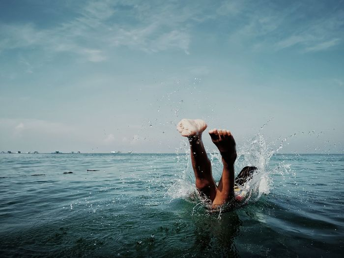 Person jumping in sea against blue sky