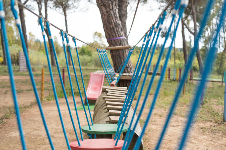 Suspended bridge in adventure playground Adventure Playground Balance Colorful Difficulty Equilibrium Exercise Game Hindrance No People Obstacle Ordeal Outdoors Park Path Problem Solving Suspended Bridge Trail Train Tree Wood