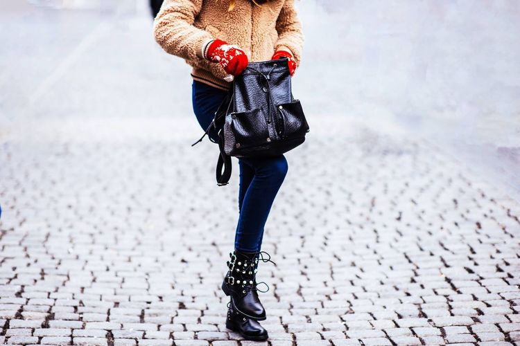 Low section of woman standing on street in winter