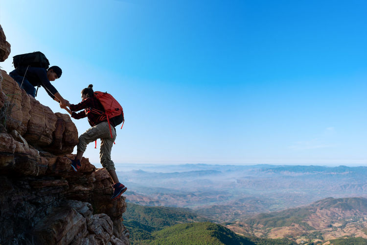 Asia couple hiking help each other in mountains view . teamwork