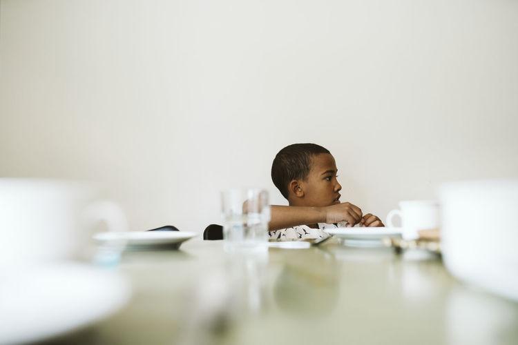 Portrait of boy sitting on table