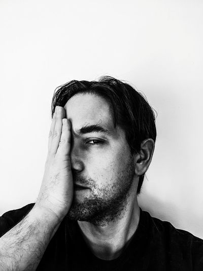 Portrait of man covering face with hand against white background