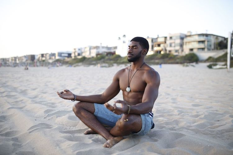 Shirtless muscular man meditating at beach against clear sky