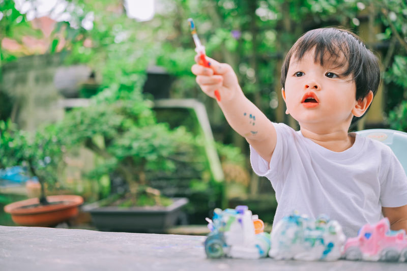 Full length of cute boy holding table