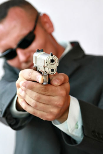 Adult Aiming Bullet Burglary Close-up Crime Danger Day Focus On Foreground Gangster Gun Handgun Holding Human Hand Men One Person People Pistol Self-defense Shooting A Weapon Spy Weapon White Background