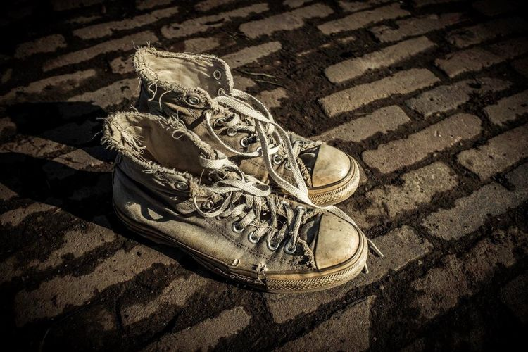 High angle view of weathered canvas shoes on footpath