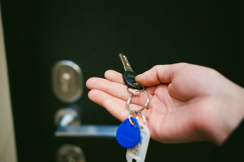 Cropped Hand Of Woman Holding Key Against Door