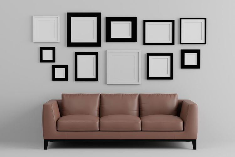 Empty Sofa Against Picture Frames On Wall At Home