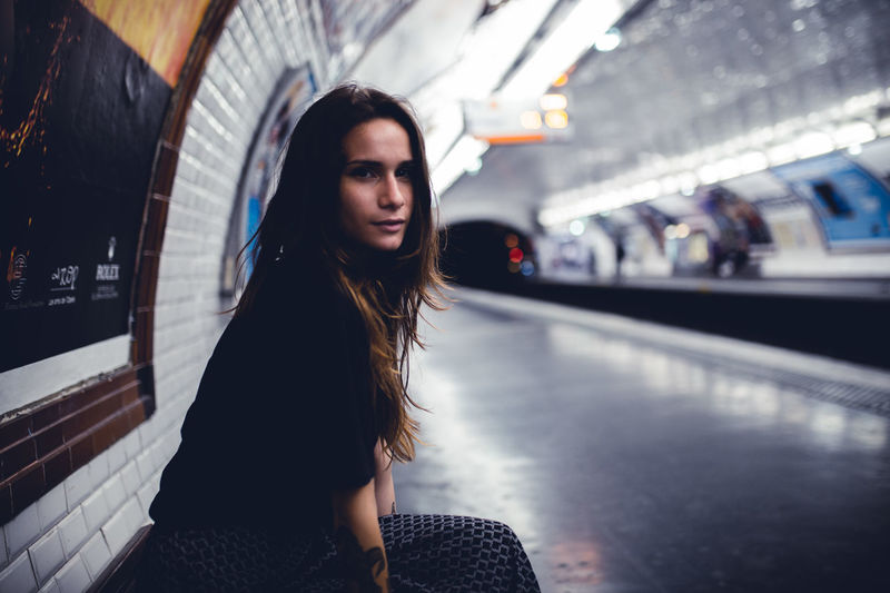 Side View Portrait Of Young Woman Sitting At Railroad Station Platform