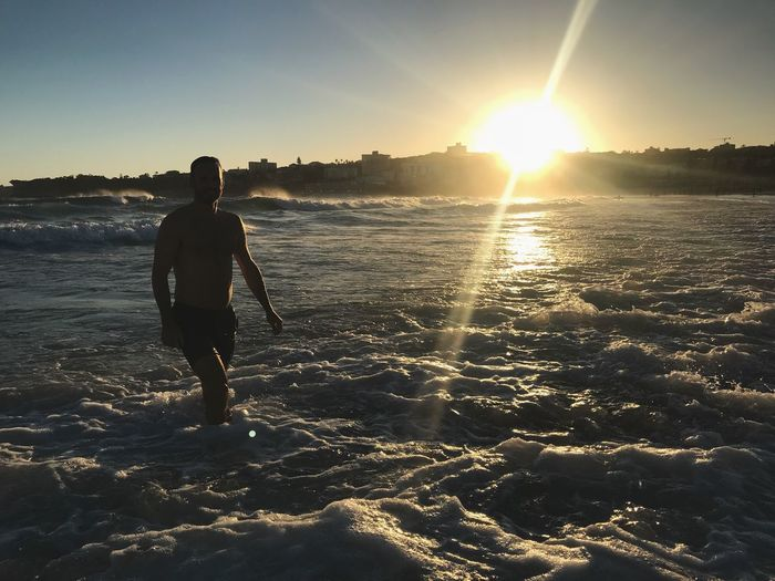 Sunset swim Beach Sky Bondi Beach Sunset Shore Waves Ocean Enjoying Life Evening Summer Fit Model Man Sky Sunlight Real People Water Sunset Beauty In Nature One Person Silhouette Nature Lifestyles Men Sun Lens Flare Full Length Leisure Activity Beach Outdoors