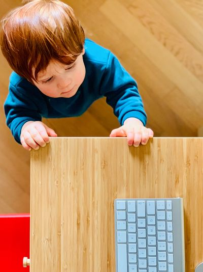 High angle view of cute baby boy looking at computer keyboard on table