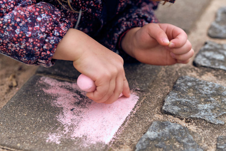 Cropped hands of girl drawing on footpath