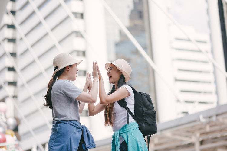 Hat Architecture Two People Three Quarter Length Built Structure Bonding Women Leisure Activity Togetherness Casual Clothing Real People Lifestyles Day Clothing Childhood Child Girls Building Exterior Standing People Outdoors Innocence