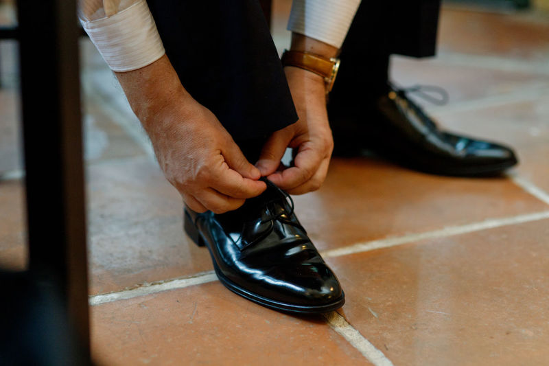 Low section of man tying shoelace on tiled floor