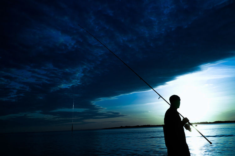 Silhouette Man Fishing In Sea Against Cloudy Sky