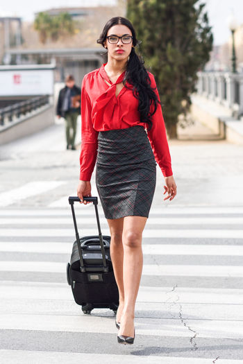 Full length portrait of businesswoman walking with luggage on street