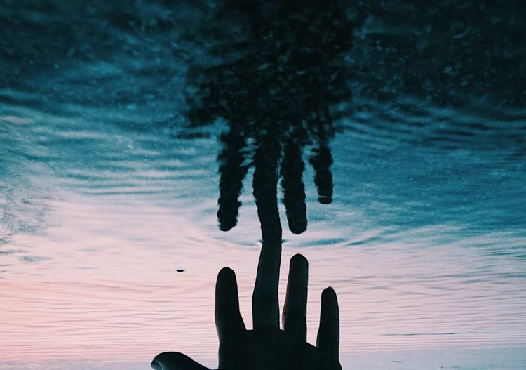 Cropped hand touching water in lake during sunset