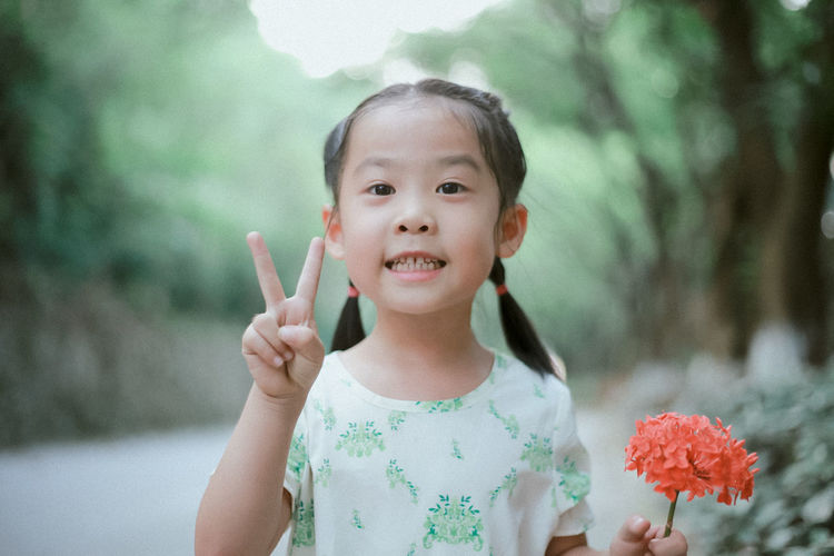 Children Childhood Close-up Day Elementary Age Flower Flowers Focus On Foreground Front View Girls Happiness Holding Human Hand Leisure Activity Lifestyles Looking At Camera Nature One Person Outdoors Portrait Real People