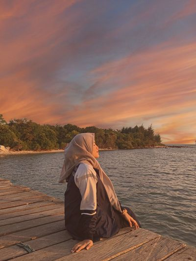 Side view of woman sitting on pier over lake against sky during sunset