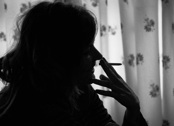 Close-up of silhouette woman smoking cigarette at home