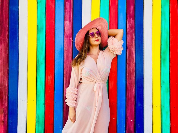Woman wearing pink dress, pink hat and fashionable sunglasses standing in front of a colorful vertical striped wall Accessory Day Front View Bright Colors Multicolors  Bright Vibrant Color Colors Colorful Stripes Striped Lines Vertical Wooden Wall Pink Sun Hat Hat Sunglasses Dress Fashionable Beach Beachwear Style Fashion Standing Young Adult Woman Summer