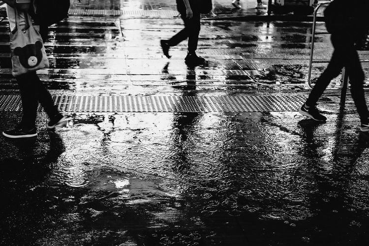 Low section of people walking on wet street during rainy season