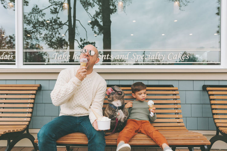 Father and son eating ice cream while sitting outdoors