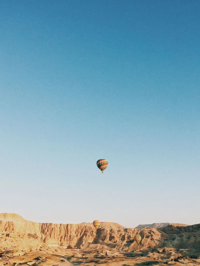 Hot air balloons flying over land against clear blue sky