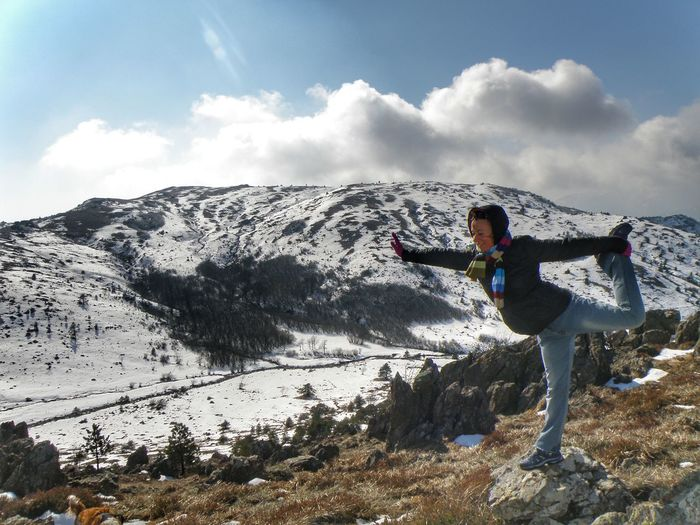 Full length of woman practicing yoga on rock against snowcapped mountain