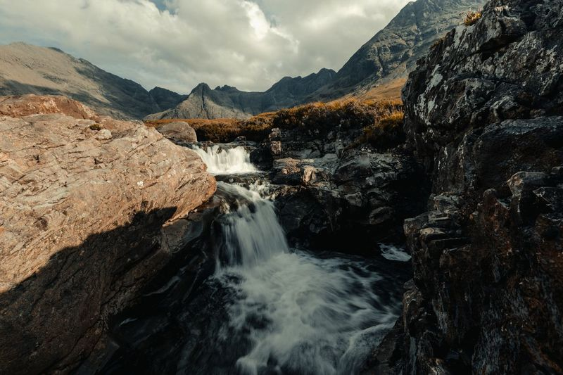 Fairy Pools, Isle of Skye, Scotland Autumn colors EyeEmNewHere Autumn Fairy Pools Isle Of Skye Skye Scotland Shadows & Lights Shadow Landscape Water Beauty In Nature Scenics - Nature Mountain Motion Cloud - Sky Sky Flowing Water Nature Rock Waterfall Mountain Range Tranquil Scene Non-urban Scene Tranquility No People Environment The Great Outdoors - 2018 EyeEm Awards
