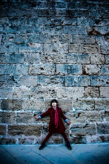 Full length of boy standing against wall
