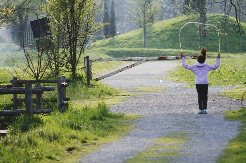 Rear View Of Girl Playing With Skipping Rope On Road