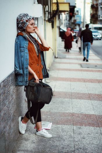 Full Length Of Woman Standing On Footpath In City