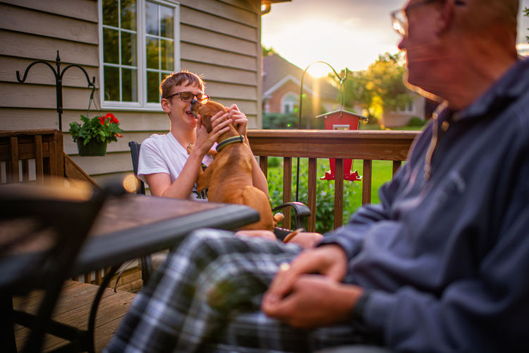 Man and boy with dog sitting at table