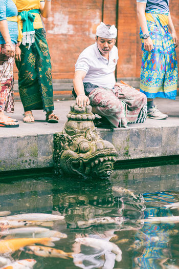 Water Temple Temple Water Adult Reflection People Men Clothing Traditional Clothing Nature Women Sitting Day Outdoors Real People Two People Occupation Sculpture Art And Craft Waterfront Bali Indonesia Bali INDONESIA