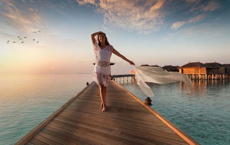 Woman Standing On Jetty Over Sea Against Sky During Sunset