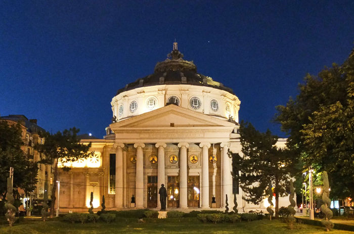 Romanian Athenaeum - Architectural Column Architecture Athenaeum Blue Building Exterior Built Structure City Clear Sky Culture Dome Dusk History Illuminated Low Angle View Night No People Outdoors Philarmonic Place Of Worship Sky Spirituality Travel Destinations Tree