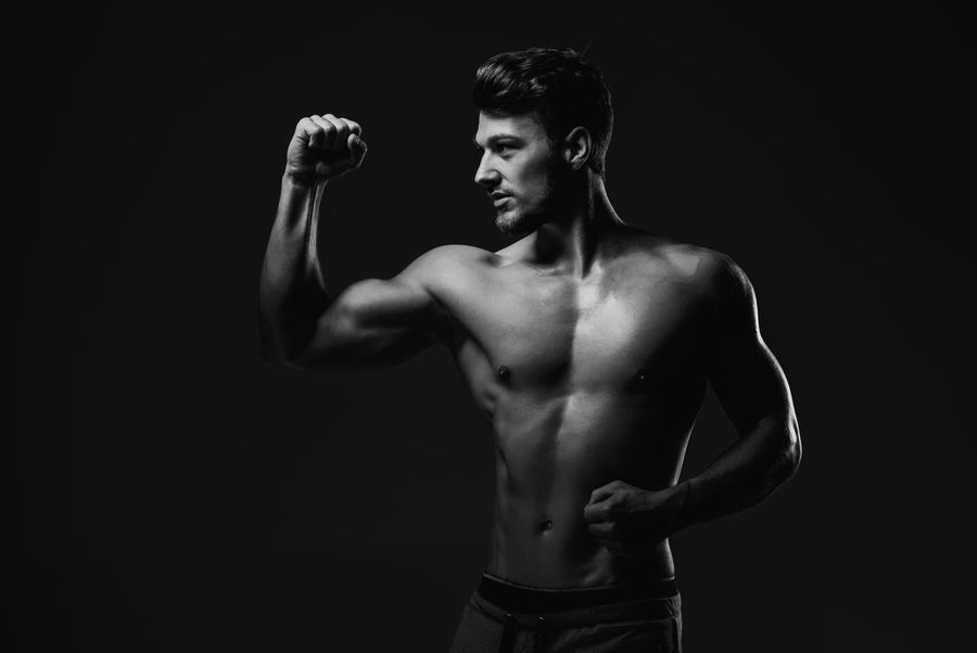 Athletic handsome man showing biceps muscles, studio shot Athlete Athletic Masculinity Abs Attractive Beauty Biceps Black And White Fitness Fitness Model Muscle Muscular Muscular Build One Person Physique  Showing Sport Sportive Sporty Standing Strong Studio Shot Torso Triceps Young Adult